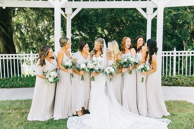 smiling bride with bridesmaids in cream