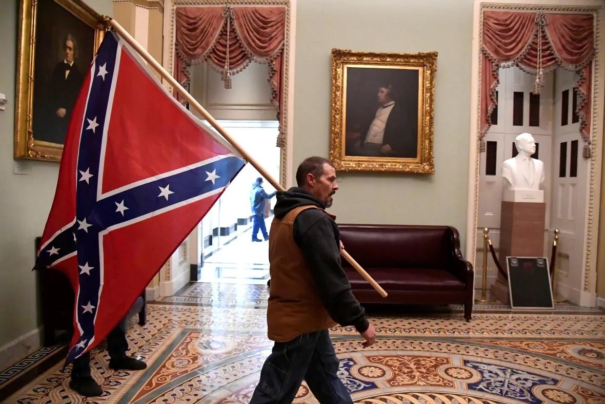 Hombre se pasea con bandera en el capitolio