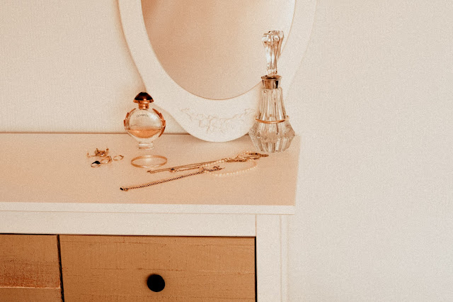 A bedroom counter top with perfumes and jewelry displayed.