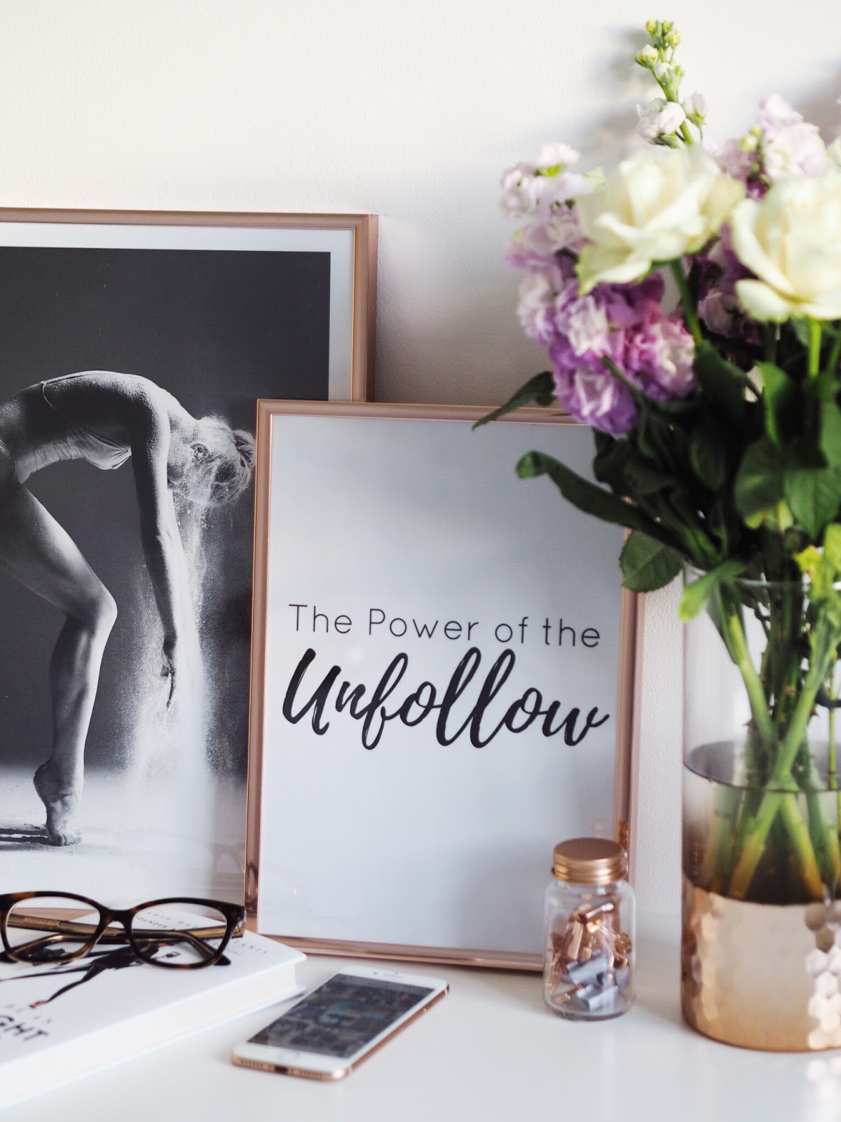 The Power of Unfollow poster in copper frame, fresh white roses and lilac stocks, glasses, ballet poster and iphone 8 with instagram open flaylay