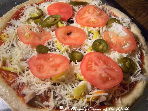 Pizza topped with tomatoes, jalapenos, mushrooms and cheese.