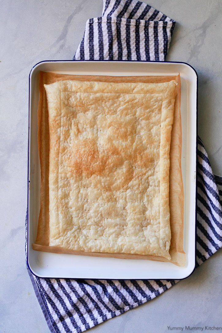 A white baking sheet with par-baked puff pastry on parchment paper.