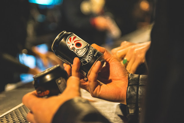 Pistonhead beer in cans being held by person wearing black leather jacket