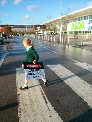 Top Ender carrying a Zombie Containment Area sign in Asda car park