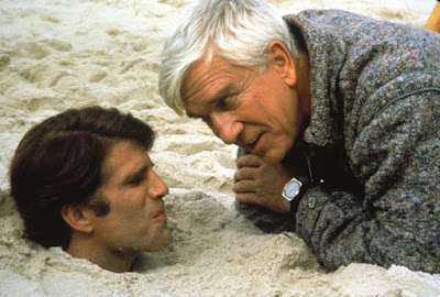 "Leslie Nielsen taunts Ted Danson, who is buried in the sand up to his neck, in a ""Creepshow"" (1982) horror movie scene"