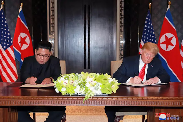Kim Jong Un and Donald Trump signing joint statement at Singapore Summit, June 12, 2018
