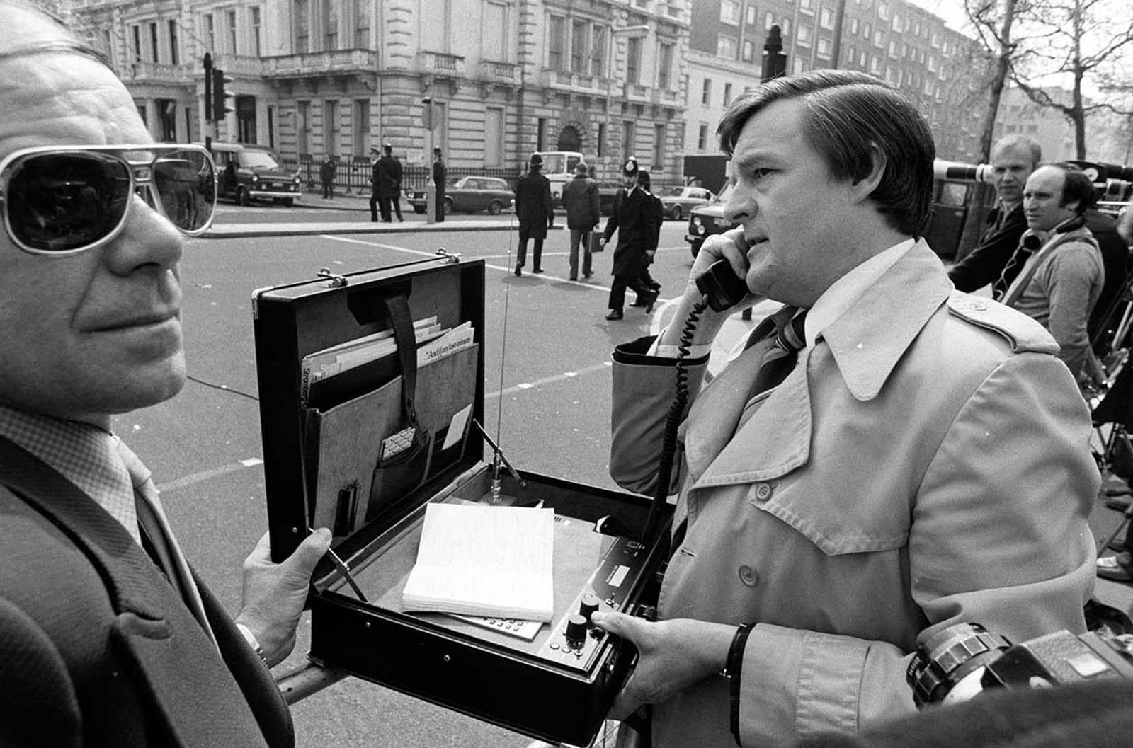An early mobile phone used by a reporter, Kensington, London. 1983.