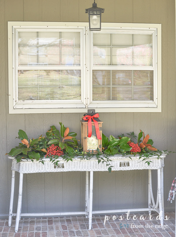 white wicker table with magnolia, nandina, and holly and wood lantern with red ribbon