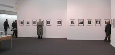 White walls and square photos evenly spaced along, two bald men looking at them