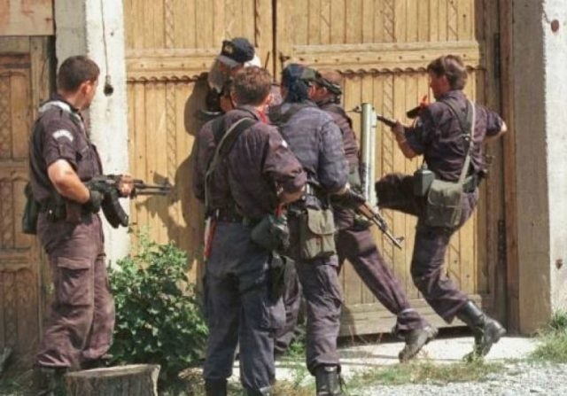 Serbian soldiers entering by force in an Albanain house