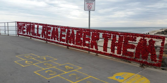 "At the start of the Brighton jetty, on the right railings, a transparent mesh banner displays the words, ""We will remember them"" in crocheted and knitted poppies. The banner has a line of red poppies around its border.  A yellow hopscotch court is painted on the jetty pavement in the foreground. Beyond the jetty, looking north, is Brighton beach. There is a signpost behind the jetty warning people not to jump or dive from the jetty. The water of St Vincents Gulf is calm with an overcast sky."
