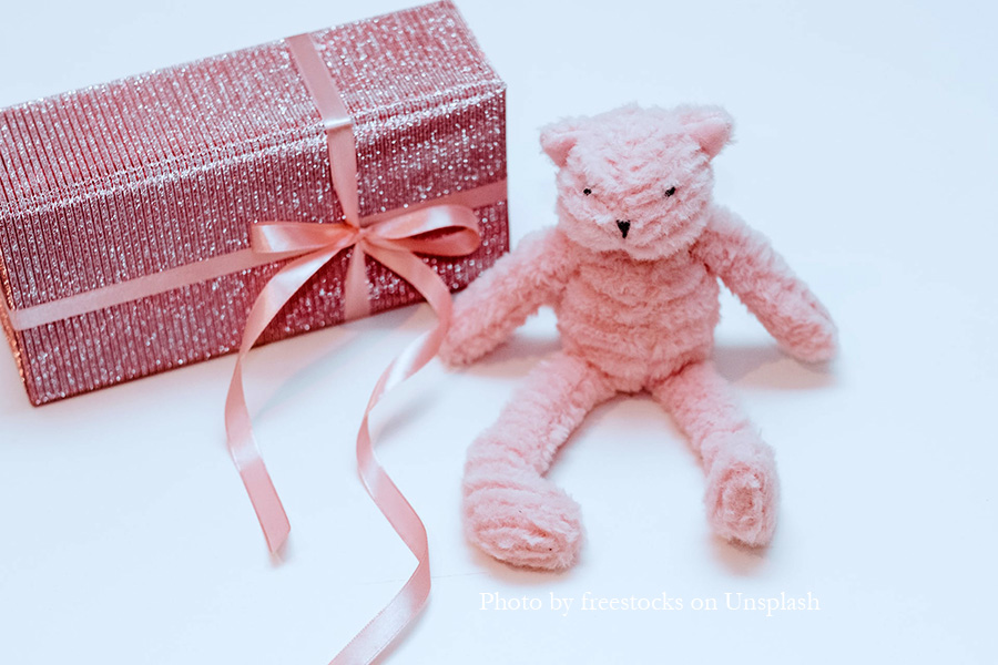 Pink teddy bear with a pink box