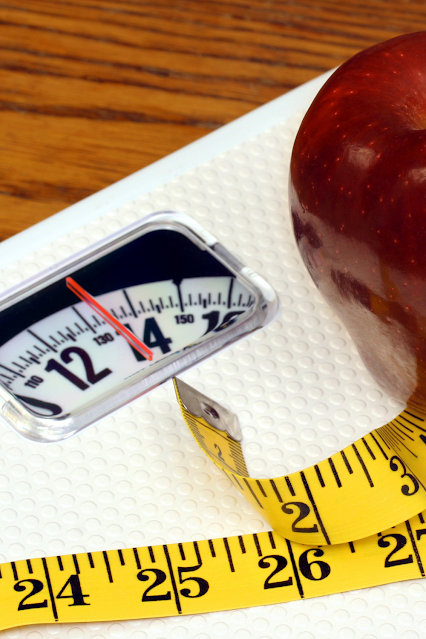 Apple and a scale to represent losing weight with a tape measure.