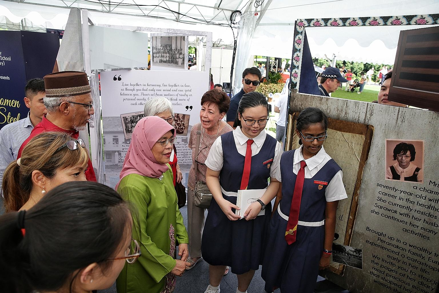 President Halimah Yacob visiting the booth of the Paya Lebar Methodist Girls' School (Secondary) at the Istana open house yesterday.