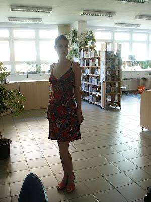 Linda stojí v prostoru knihovny