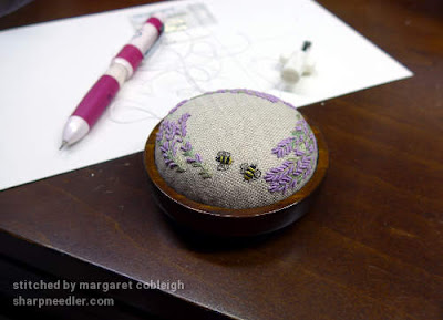 Embroidery mounted in pincushion base after being laced to the form