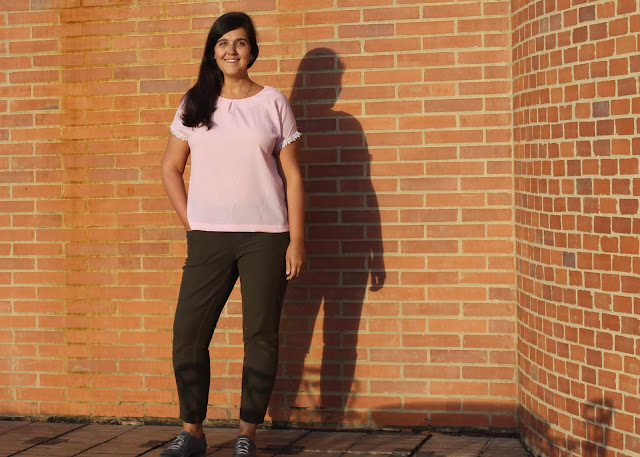A woman wearing olive green jeans and a pink crepe top made from the Avid Seamstress Drop-Sleeved Top sewing pattern.