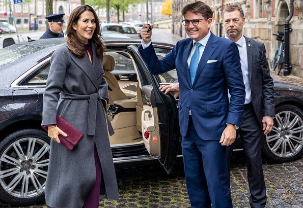 At the award ceremony, Crown Princess Mary wore a burgundy silk mock neck belted top and trousers, and grey cashmere wool long coat