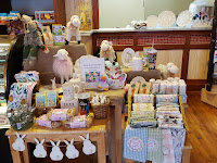 various Easter gifts and decor like floral tea towels and a white bunny bunting are arranged in baskets and wooden tables at Palmer's Candy in Sioux City