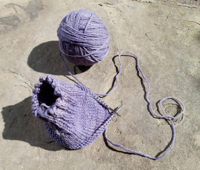 Image shows a partly-knitted purple sock and a ball of purple yarn sitting on a stone paving flag in the sunshine