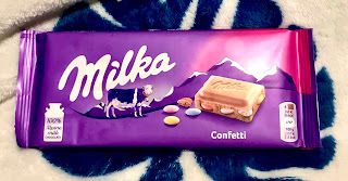 A rectangular purple bar with milk in white font with a picture of a brown square chocolate piece with circular colourful candy pieces coming out of it with Confetti in white font below on a bright background