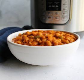 looking across a bowl of homemade maple baked beans with pressure cooker in background