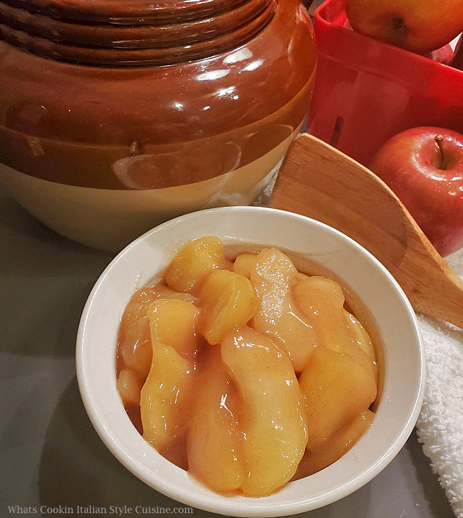 this is a top shot of country fried apples in a white ramekin bowl. In the background is a big brown bean pot, wooden spoon and whole apples with a white bar cloth