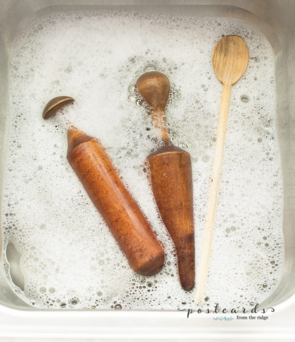 vintage wooden utensils in warm soapy water