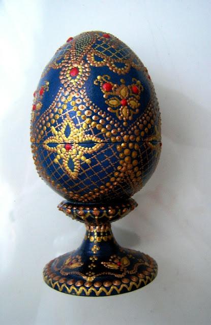 Такие прекрасные декоративные яйца вы можете изготовить самостоятельно, даже если не имеете способностей к рисованию. Основная задача — перенести на яйцо-заготовку контур понравившегося рисунка. Это можно сделать с помощью шаблонов и простого карандаша. Но для начала вам нужно загрунтовать яйцо и покрасить его в желаемый цвет. После высыхания заготовки нанесите контуры рисунка, а затем берите краски нужного цвета, тонкую кисть и начинайте наносить аккуратные точки и штрихи. Не забывайте делать промежуточные просушки точек, чтобы краски случайно не смешались и не смазались. Последовательность нанесендекор пасхальный, декор яиц, Пасха, подарки пасхальные, рукоделие пасхальное, яйца, яйца пасхальные, яйца пасхальные декоративные, роспись, роспись точечная, оформление красками, оформление росписью, ия точек вы можете рассчитать самостоятельно, в зависимости от сложности рисунка.