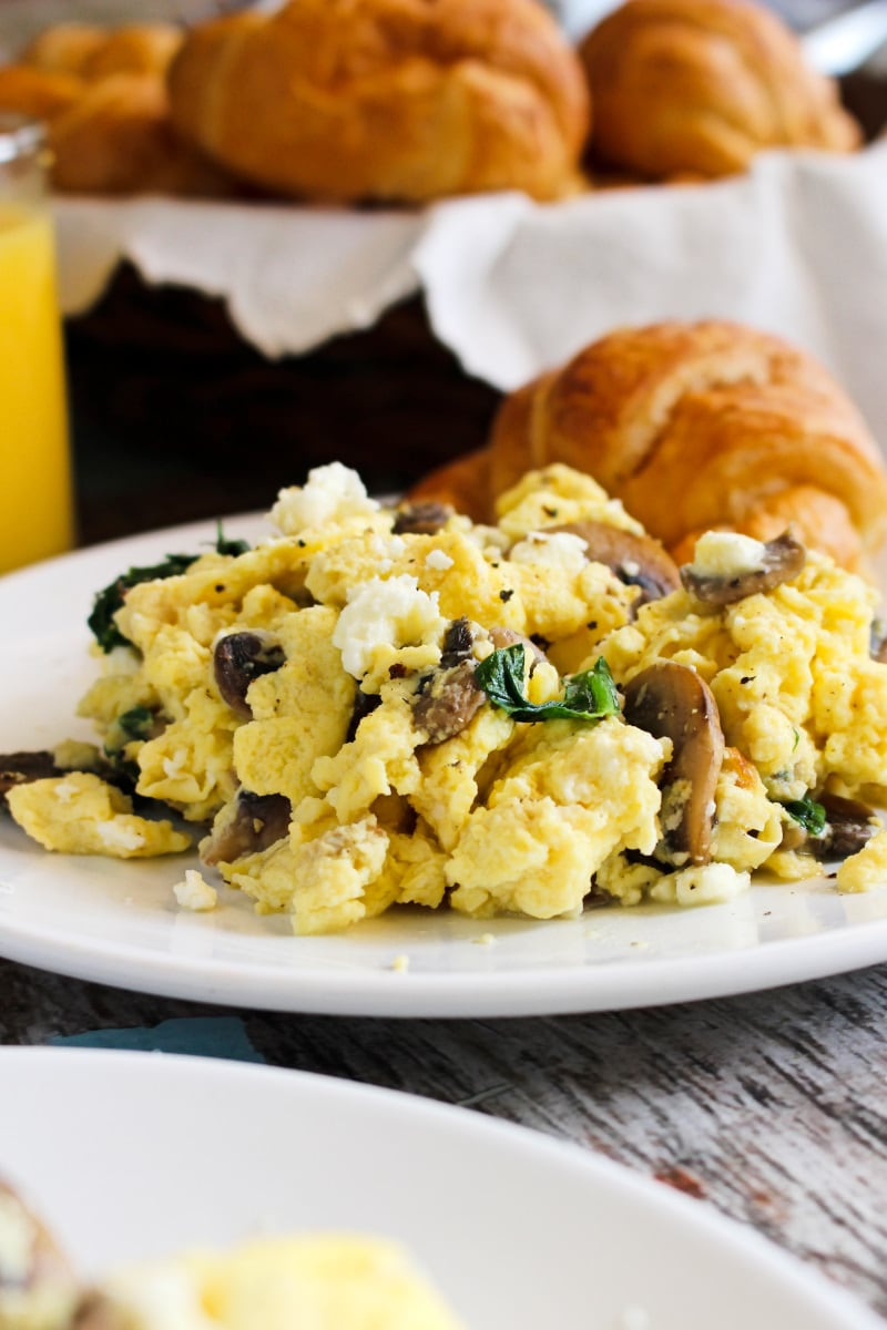 Side view of scrambled eggs with mushrooms, feta, and spinach on a white plate.