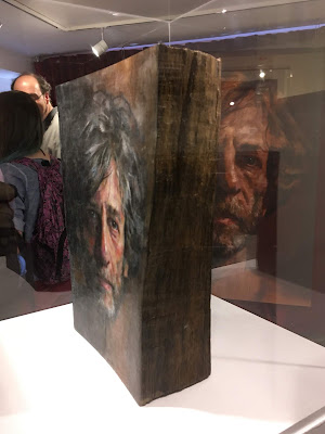 photo of display case holding a wooden book, on the cover of which is painted a portrait of Neil Gaiman
