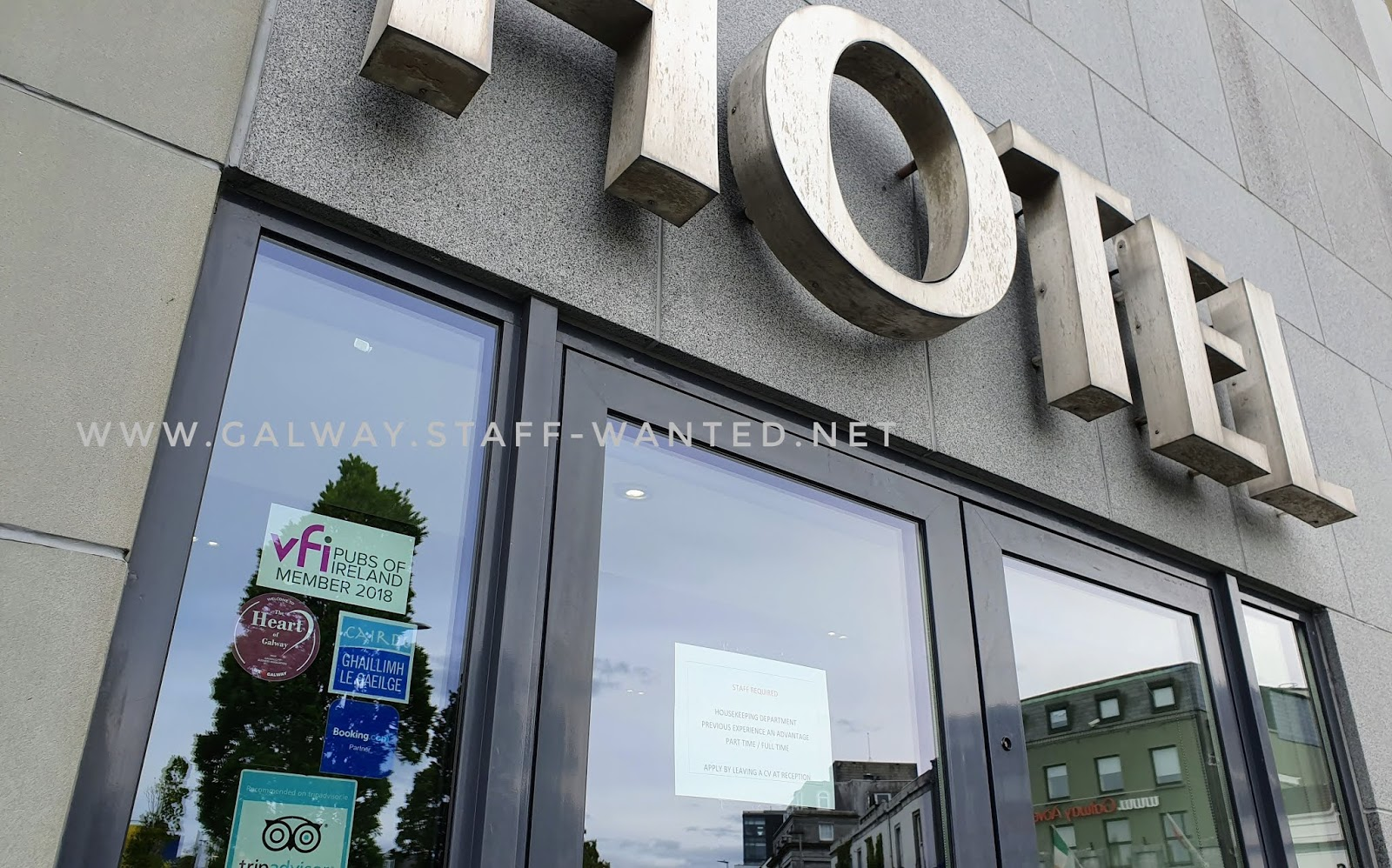 Modern hotel front window, with stickers from the Vinters Federation of Ireland (Member, 2018), the Heart of Galway (Galway Business Association), Booking.com partner , Carido / Ghaillimh le Gaeilge, and Tripadvisorr