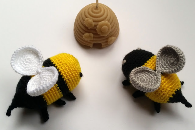 Top view of two bees facing the beehive candle. One can see the round shapes of the wings.