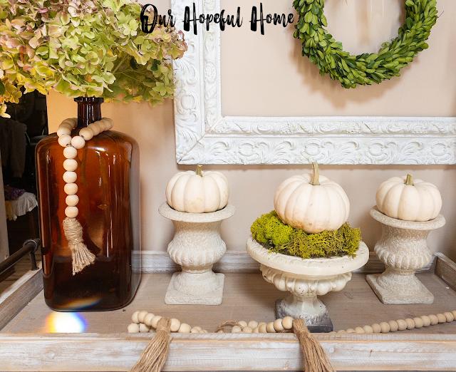 three French urns white baby boo pumpkins amber vase