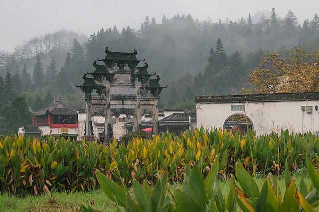 Arche Ming à trois niveaux et collines embrumées à Xidi