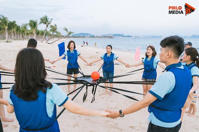 Mọi người vui vẻ khi chụp ảnh team building ở bãi biển Hạ Long, cùng chơi với trái bóng