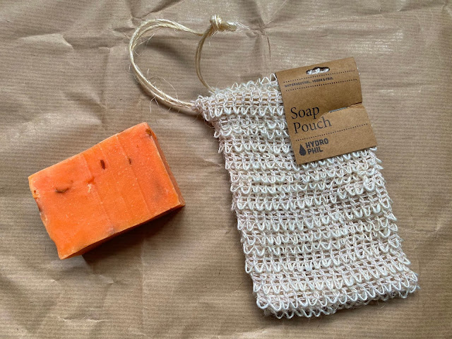 an orange scented block of soap next to a sisal knitted soap pouch