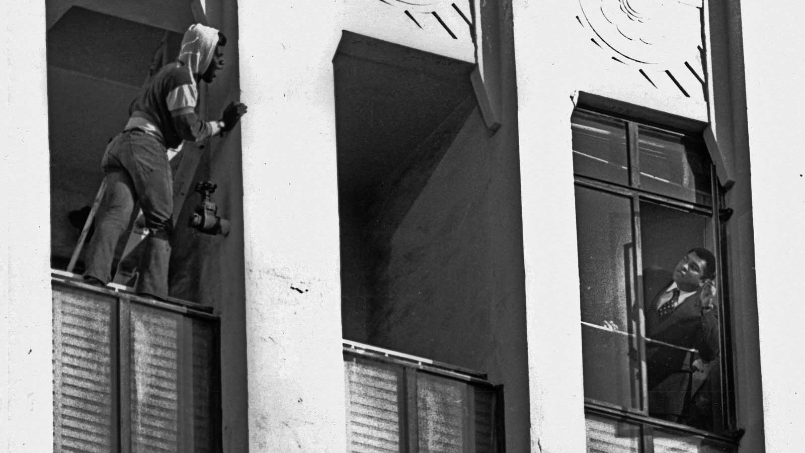 This is the dramatic moment Muhammad Ali saved a suicidal man who was threatening to jump out of a ninth-floor building in Los Angeles in 1981. Ali (right) is seen leaning out of a window pleading with the man.