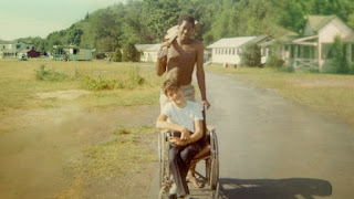 In a scene from the documentary, a young Black camp counselor stands behind a white teenage young man in a wheelchair. Behind them is a rolling green hill with white buildings that are camp dormitories
