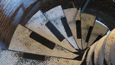 Looking down a spiral staircase with black treads at the edge of white steps. A curved brick wall is at the left.