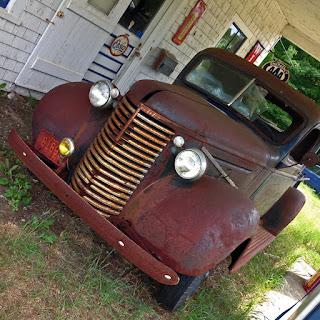 Old pickup truck waiting alongside gasoline pumps.