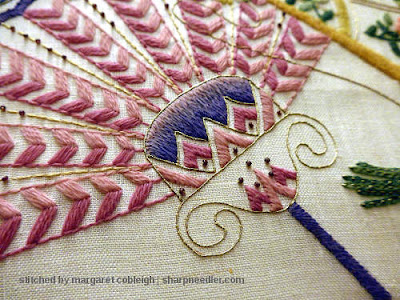 Close-up of pink fan from vintage commcerical crewel kit