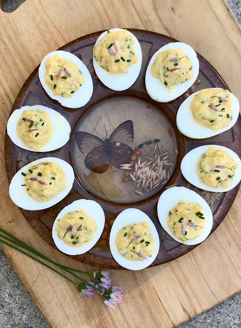 Chive blosson deviled eggs on a deviled egg plate.