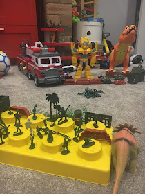 Kids army battle set up with dinosaurs, transformer bumblebee and lego