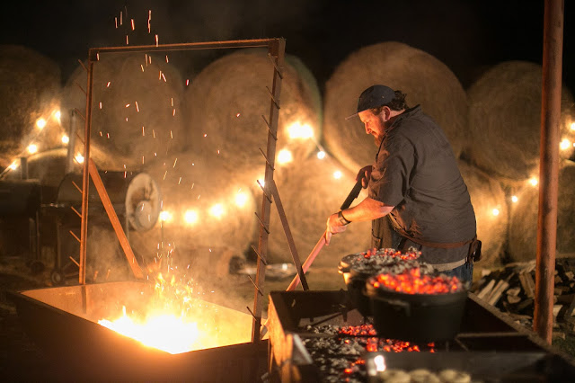 Jay Ducote works the mother fire at the Pineywoods Supper Club while biscuits cook in Dutch ovens