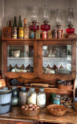 This baker's cabinet is straight out of a classic farmhouse style kitchen with mason jar storage containers and wicker baskets