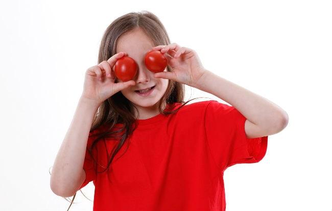 Bambina che gioca con le verdure