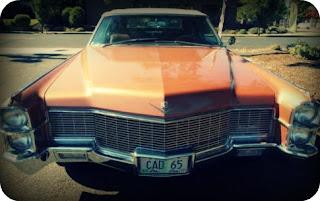 Illusztráció vershez, hibátlan állapotú narancsmetál színű 1965 Cadillac Coupe DeVille Convertible napsütötte parkolóban, hűtőrács irányából fotózva.