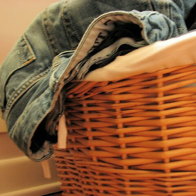Wicker laundry basket with jeans hanging out of the top