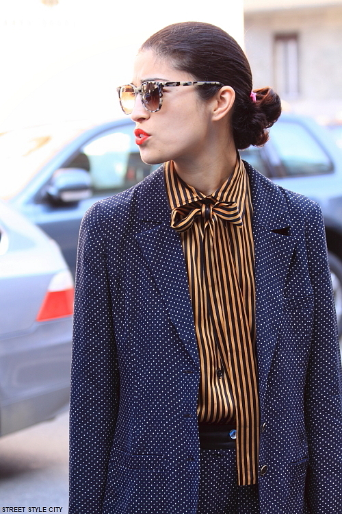 Woman wearing striped blouse and dots in the street of Milan. Street style fashion.
